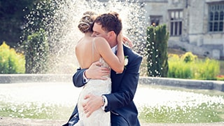 brent-kirkman-sony-alpha-9-newly-married-couple-embrace-in-front-of-fountain