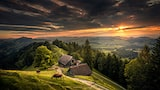 ilhan-eroglu-sony-alpha-7RIII-cows-grazing-on-mountainside-with-chalet-lit-by-dramatic-sun-through-storm-clouds