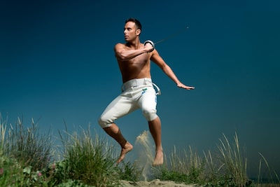 maki-galimberti-sony-alpha-7RII-man-with-fencing-sword-jumps-in-the-air-outside-on-beach